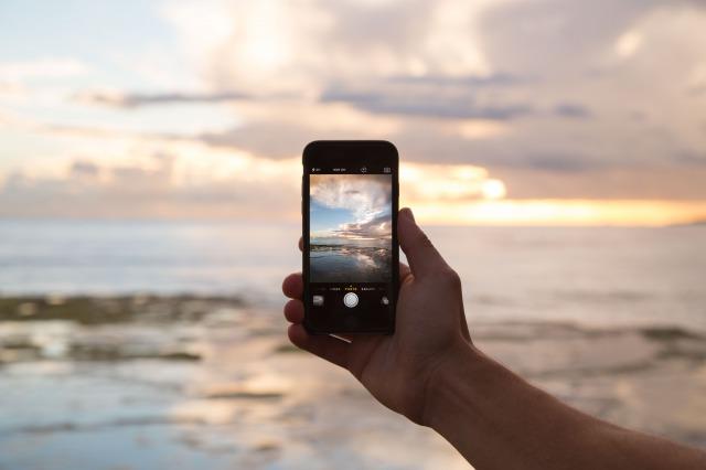 スマホで海と空を撮影する人の手