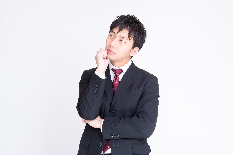 悩んでいるスーツを着た男性の画像
